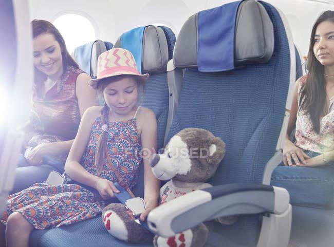Girl fastening seat belt on stuffed animal on airplane — Stock Photo