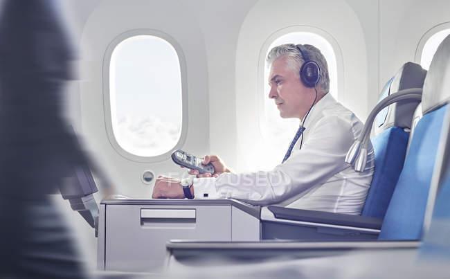 Homme d'affaires avec écouteurs et télécommande regarder film sur avion — Photo de stock