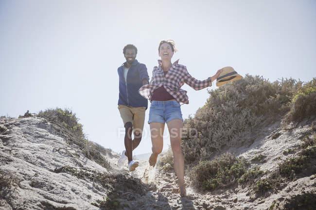 Verspielt, energetische multiethnischen paar laufen auf sonnigen Sommer Sand Strand Weg — Stockfoto