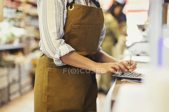 Female cashier using calculator in grocery store — Stock Photo