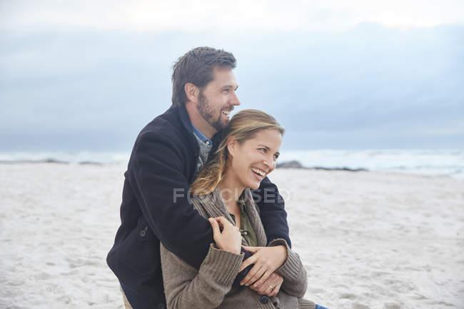 Happy couple hugging on winter beach — Stock Photo