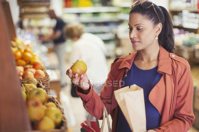 Mulher, shopping, examinando a maçã na mercearia — Fotografia de Stock