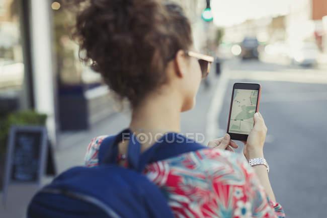 Joven turista con mochila usando el Gps en el teléfono inteligente en la calle urbanita - foto de stock