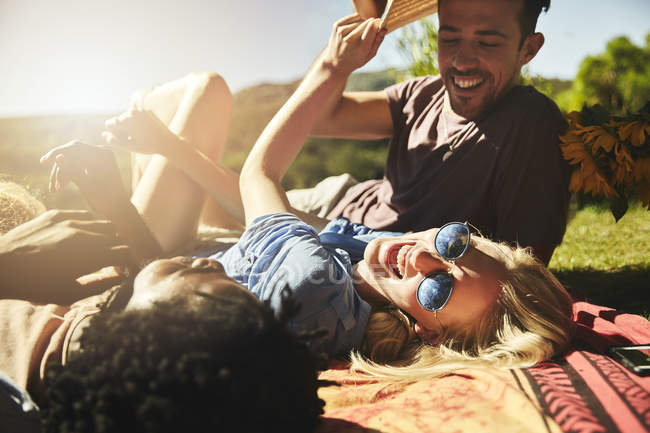 Playful young friends laughing, relaxing on picnic blanket in sunny summer park — Stock Photo