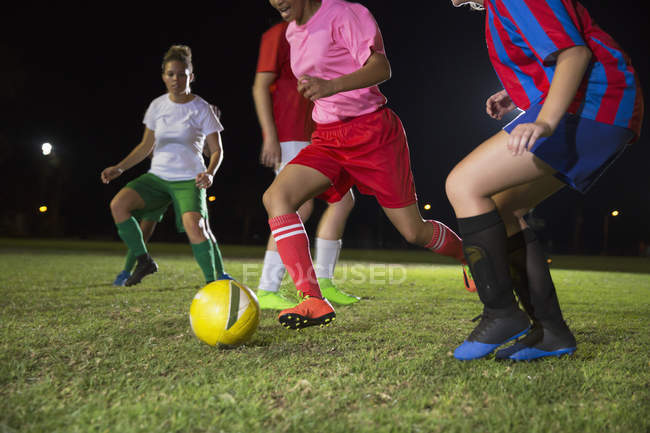 Жіночий футбол гравці грають на полі на ніч, які підуть за м'яч — стокове фото
