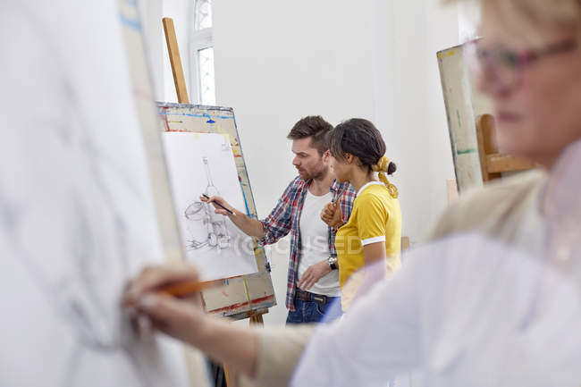 Artists discussing sketch at easel in art class studio — Stock Photo