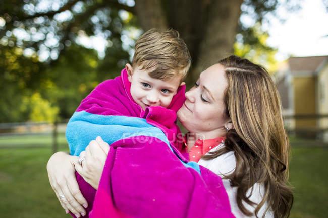 Mère affectueuse tenant son fils enveloppé dans une serviette dans la cour d'été — Photo de stock