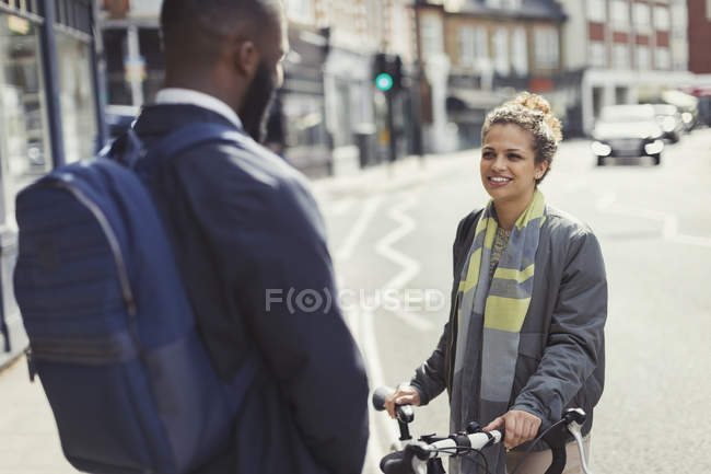 Friends with bicycle talking on sunny urban street — Stock Photo