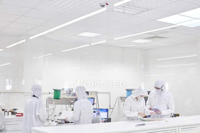 Инженеры в чистых костюмах с использованием оборудования в лаборатории исследования и тестирования волоконной оптики — стоковое фото