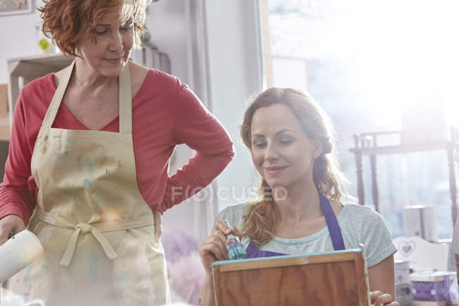 Female artists painting wood in art class workshop — Stock Photo