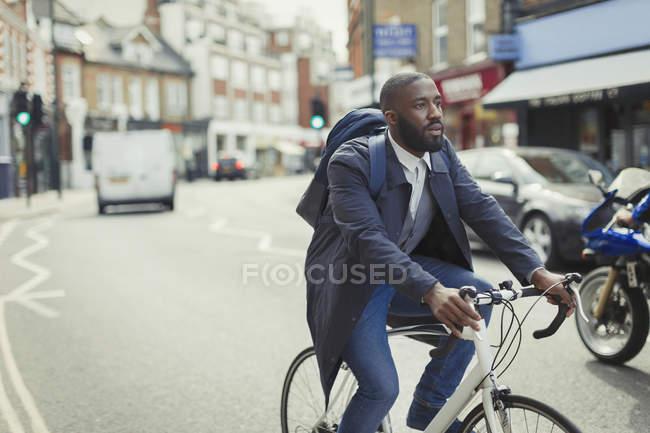 Businessman pendolarismo, andare in bicicletta sulla strada urbana — Foto stock
