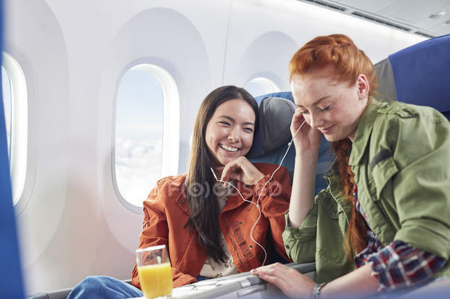Young women friends sharing headphones, listening to music on airplane — Stock Photo