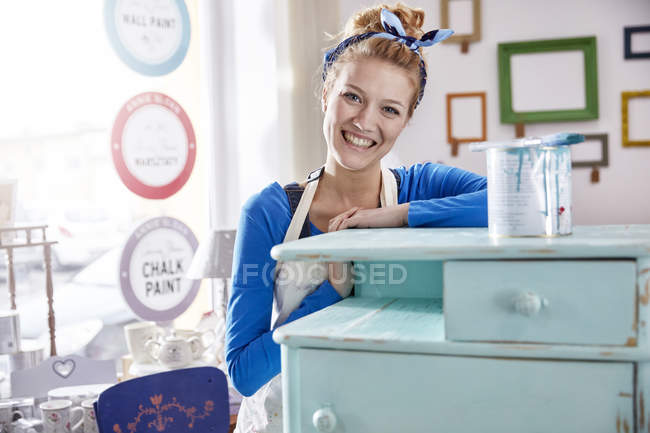 Portrait smiling, confident female artist painting side table blue in art class workshop — Stock Photo