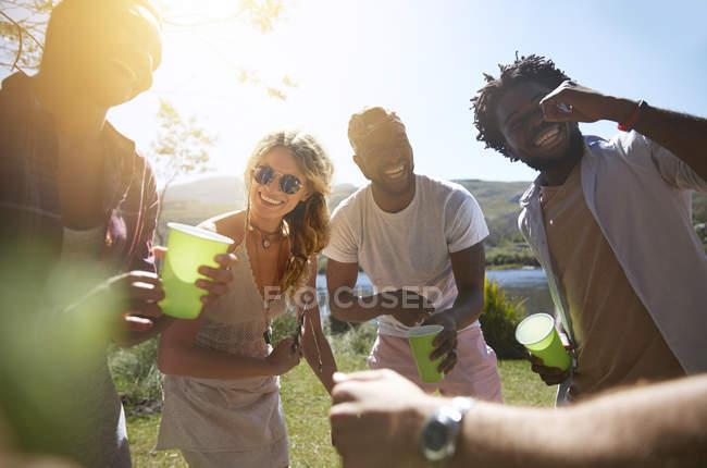 Lachende junge Freunde, die trinken und im sonnigen Sommerpark abhängen — Stockfoto
