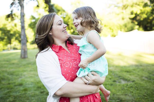 Посміхаючись, Ласкавий матері, проведення дочка в літній трава двір — стокове фото