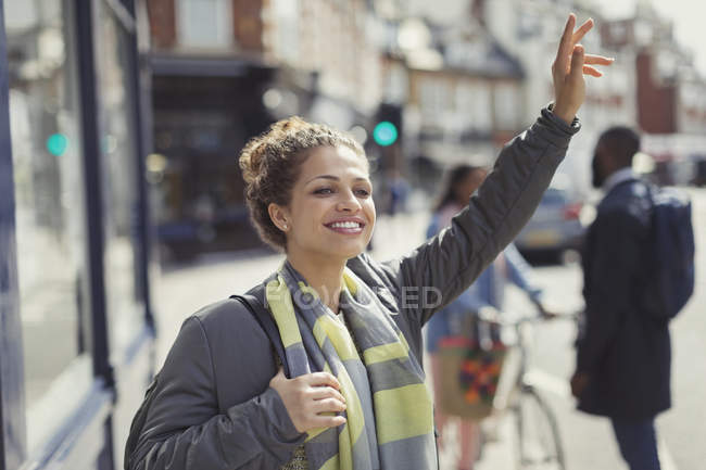 Smiling young woman hailing taxi on sunny urban street — Stock Photo