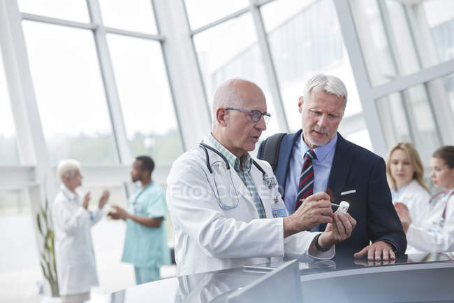 Male doctor and pharmaceutical representative discussing medication in hospital lobby — Stock Photo