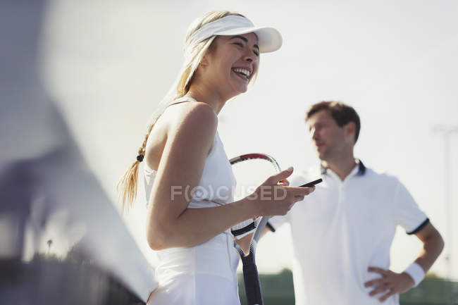Laughing female tennis player holding cell phone and tennis racket — Stock Photo