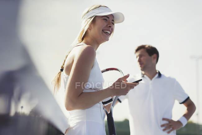 Смеющийся женский теннисный игрок Холдинг сотовый телефон и теннисные ракетки — стоковое фото