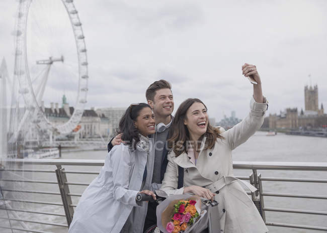 Smiling, happy friends taking selfie with selfie stick on bridge near Millennium Wheel, London, UK — Stock Photo