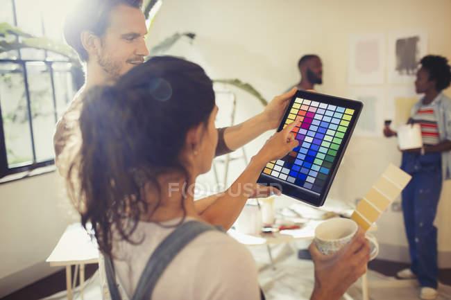 Amigos con digital tablet viendo muestras de pintura digital, pintura sala de estar - foto de stock