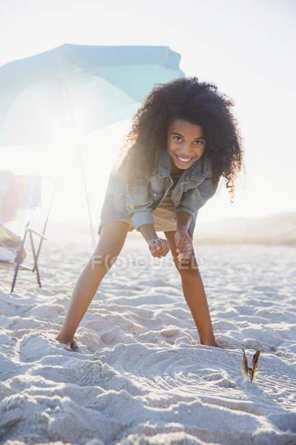 Retrato sonriente, chica preadolescente confiada doblando en la soleada playa de verano - foto de stock