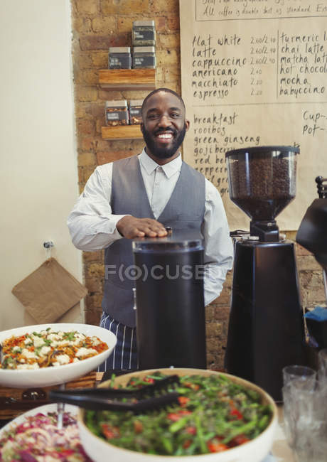 Portrait smiling male barista working behind counter in cafe — Stock Photo