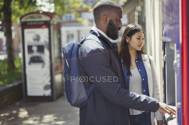 Young couple using urban ATM — Stockfoto