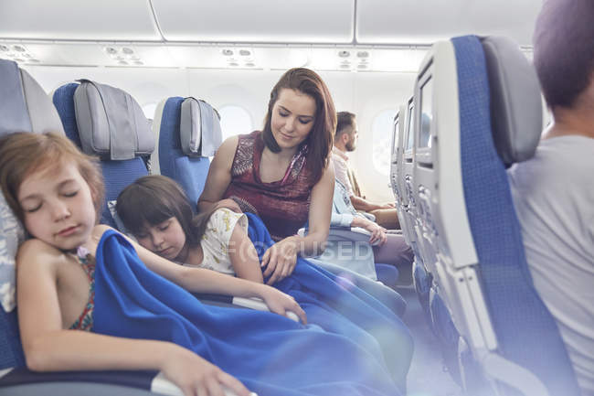 Mother putting blanket on sleeping daughter on airplane — Stock Photo