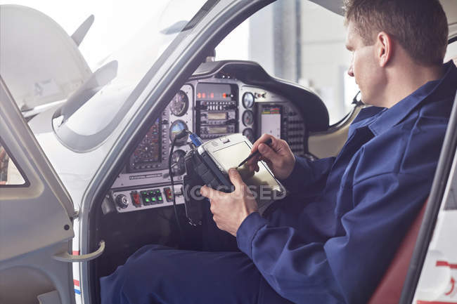 Ingenieur überprüft Diagnose mit digitalem Tablet im Flugzeug-Cockpit — Stockfoto