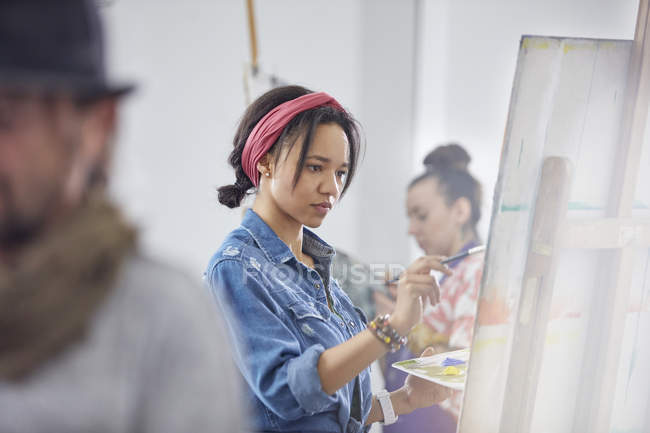 Focused female artist painting at easel in art class studio — Stock Photo