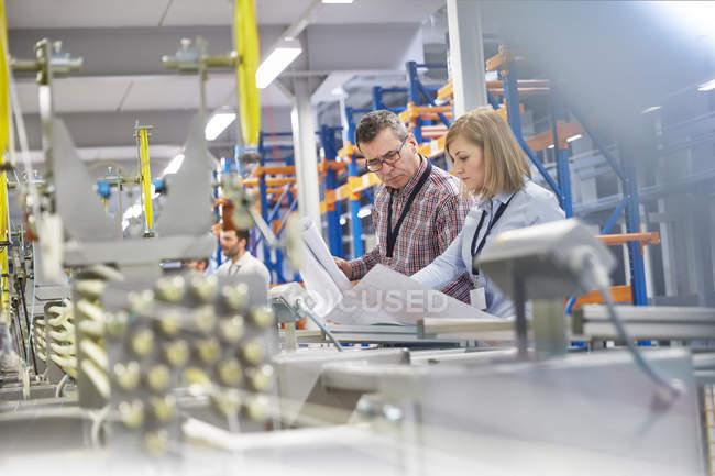 Superviseur et ingénieur discutant des plans dans l'usine de fibre optique — Photo de stock