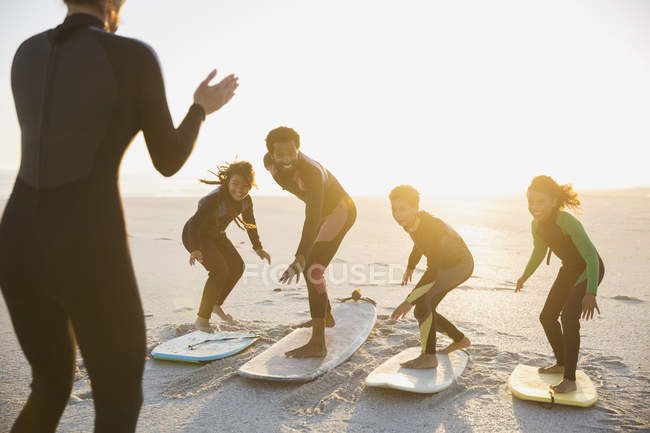 Surfer instructor teaching family on surfboards surfing on sunny summer sunset beach — Stock Photo
