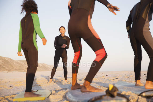 Young female surfer teaching family surfing on surfboards on sunny summer beach — Stock Photo