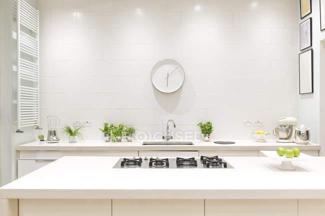 Blanco, casa de lujo moderno escaparate cocina interior con reloj - foto de stock