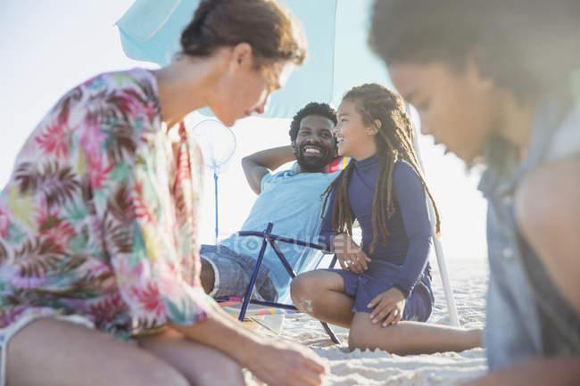 Family relaxing on sunny summer beach — Stock Photo