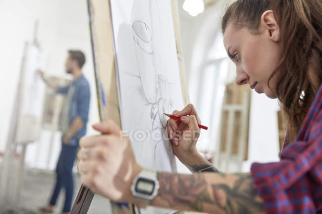 Focused female artist with tattoo sketching at easel in art class studio — Stock Photo