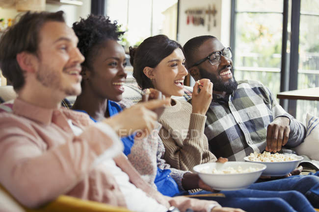 Smiling couples watching movie, eating popcorn — Stock Photo