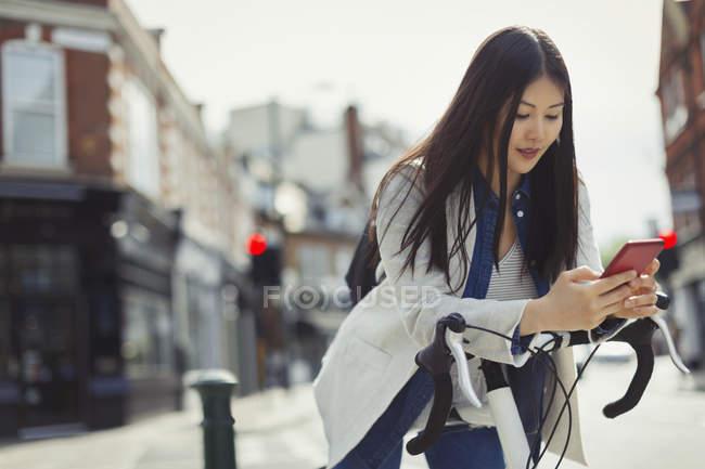 Mujer joven viajando en bicicleta, mensajes de texto con teléfono celular en la calle urbana soleada - foto de stock