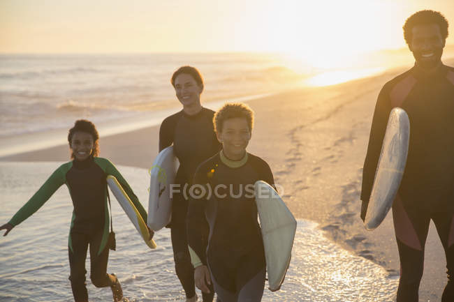 Family surfers walking with surfboards on sunny summer sunset ocean beach — Stock Photo