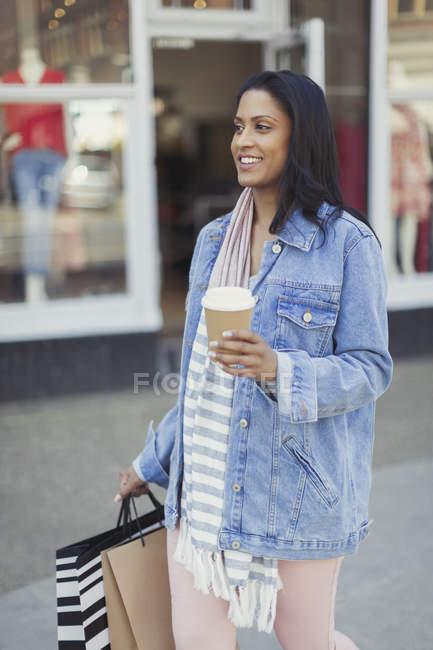 Sorrindo mulher andando ao longo da frente da loja com café e sacos de compras — Fotografia de Stock