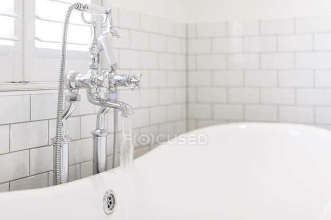 Eau qui coule du robinet de salle de bain en blanc une baignoire — Photo de stock