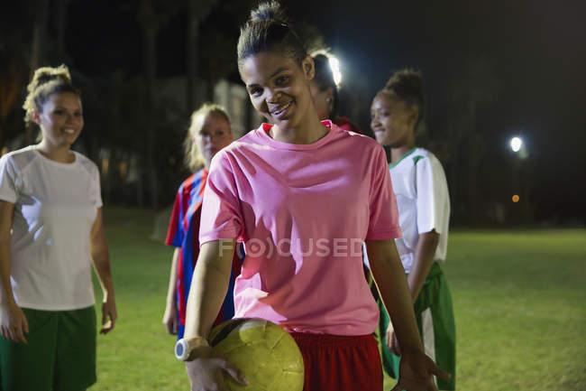 Портрет улыбающейся, уверенной в себе молодой футболистки с мячом на поле ночью — стоковое фото