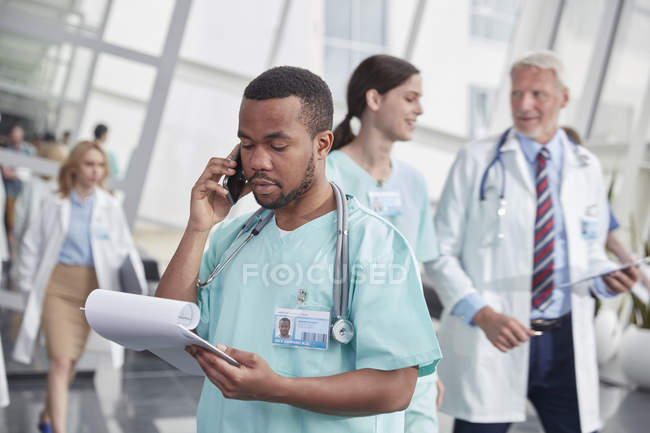 Male nurse with clipboard talking on cell phone in hospital corridor — Stock Photo