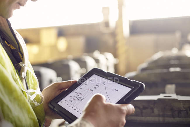 Close up steelworker reviewing digital graph on digital tablet in steel mill — Stock Photo