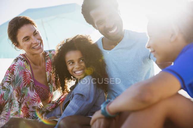 Familia multiétnica hablando juntos en la playa - foto de stock