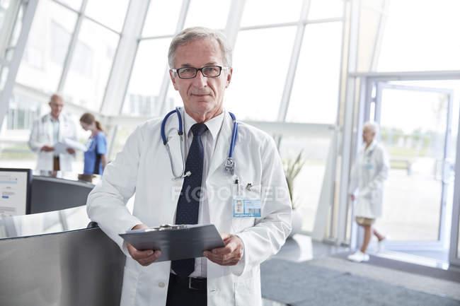 Porträt selbstbewusster Oberarzt mit Klemmbrett in Krankenhauslobby — Stockfoto