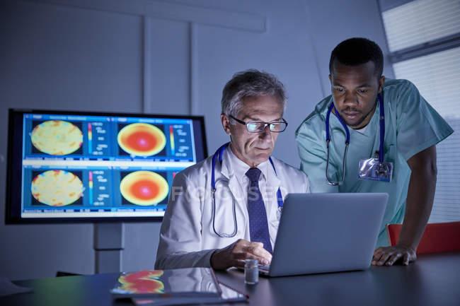 Cirurgião e médico trabalhando em laptop na sala de conferências do hospital — Fotografia de Stock
