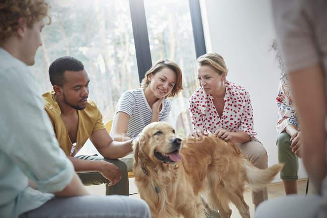 Personnes caressant chien en thérapie de groupe — Photo de stock
