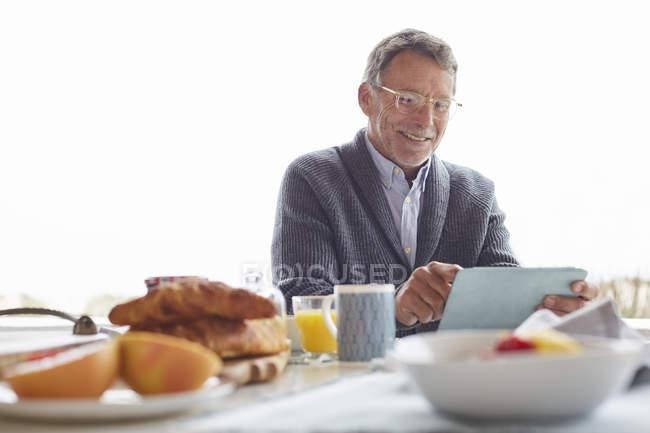 Senior nutzt digitales Tablet beim Frühstück auf der Terrasse — Stockfoto
